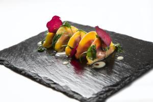 Aqualux Hotel Spa Suite & Terme  Restaurant EVO Ravioli gefüllt mit roter Beete und angerichtet mit Rapunzeln und geräuchertem Käse