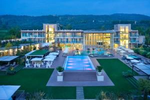 Aqualux Hotel Spa Suite & Terme mit Garten und Poollandschaft in der Abenddämmerung